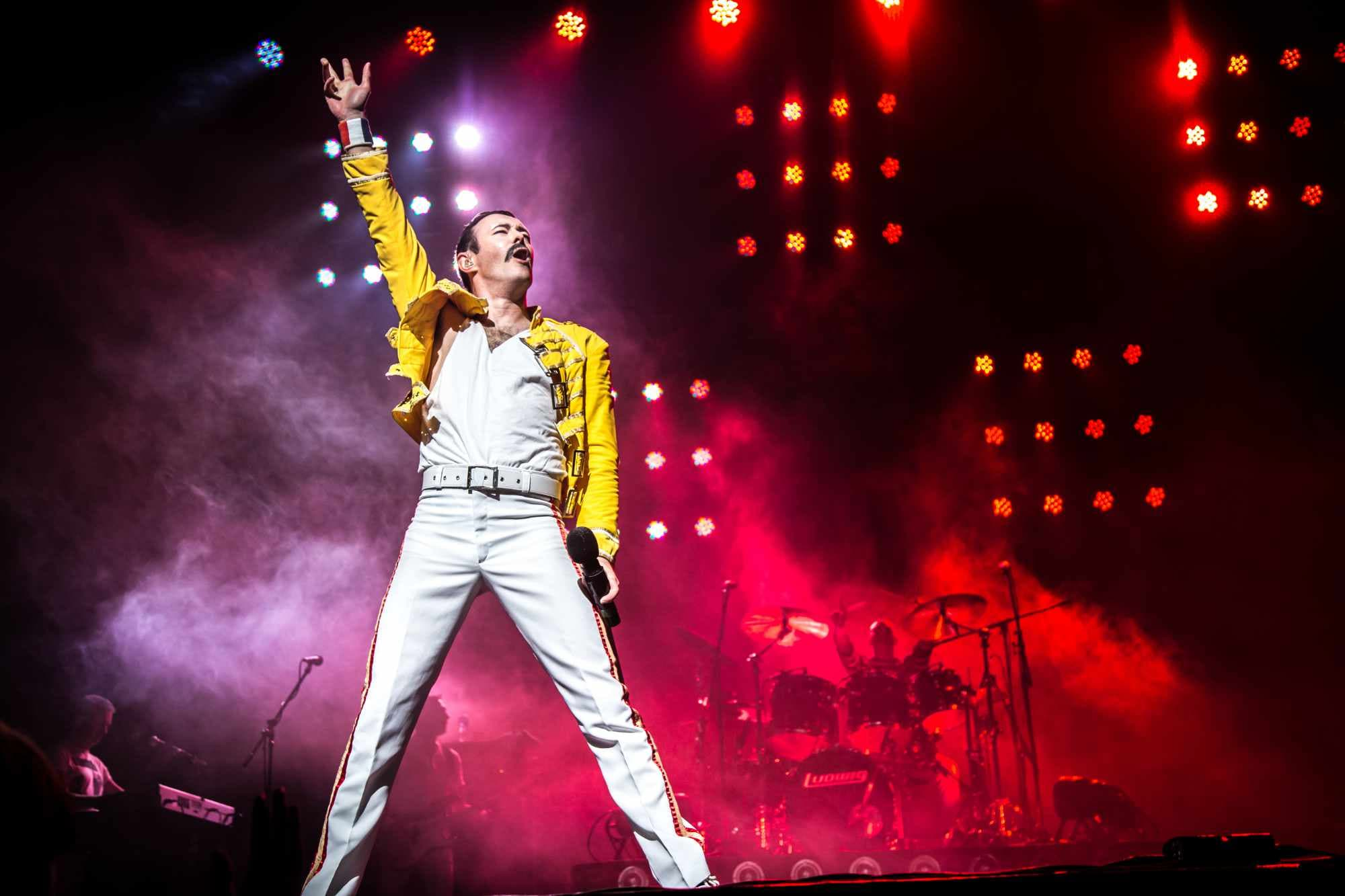 A photo of the frontman of One Night of Queen (dressed as Freddie Mercury) posing on-stage with his fist in the air.